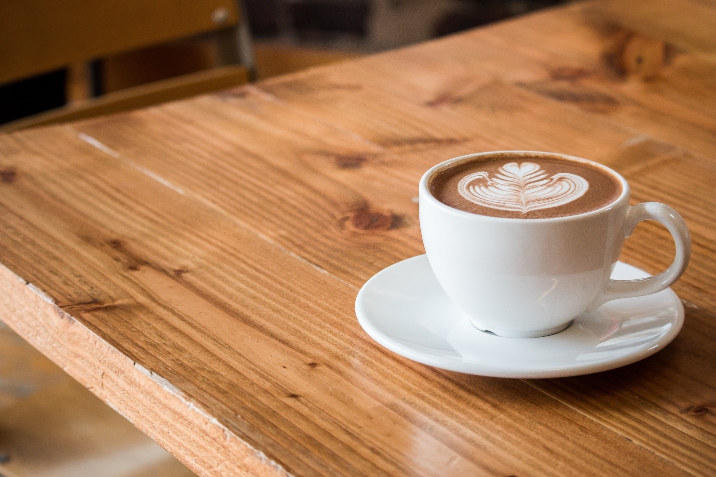A cup of coffee on a wooden coffee table